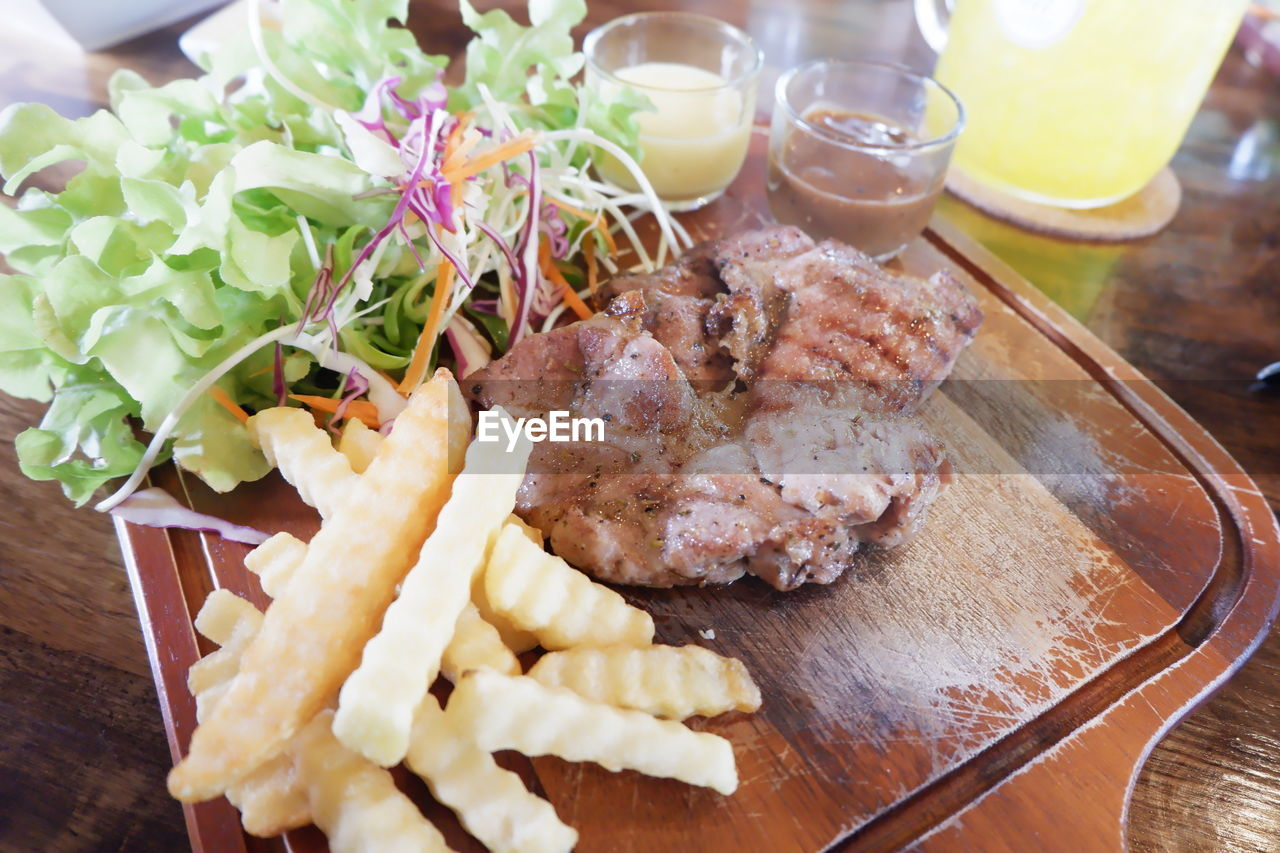 food and drink, food, freshness, ready-to-eat, table, meat, indoors, close-up, high angle view, no people, still life, plate, serving size, meal, healthy eating, prepared potato, potato, wood - material, french fries, vegetable, glass, temptation, garnish, snack