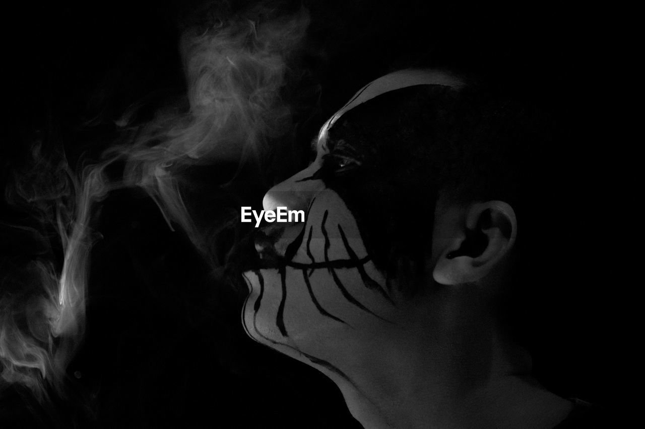 Side View Of Man With Face Paint Emitting Smoke Against Black Background