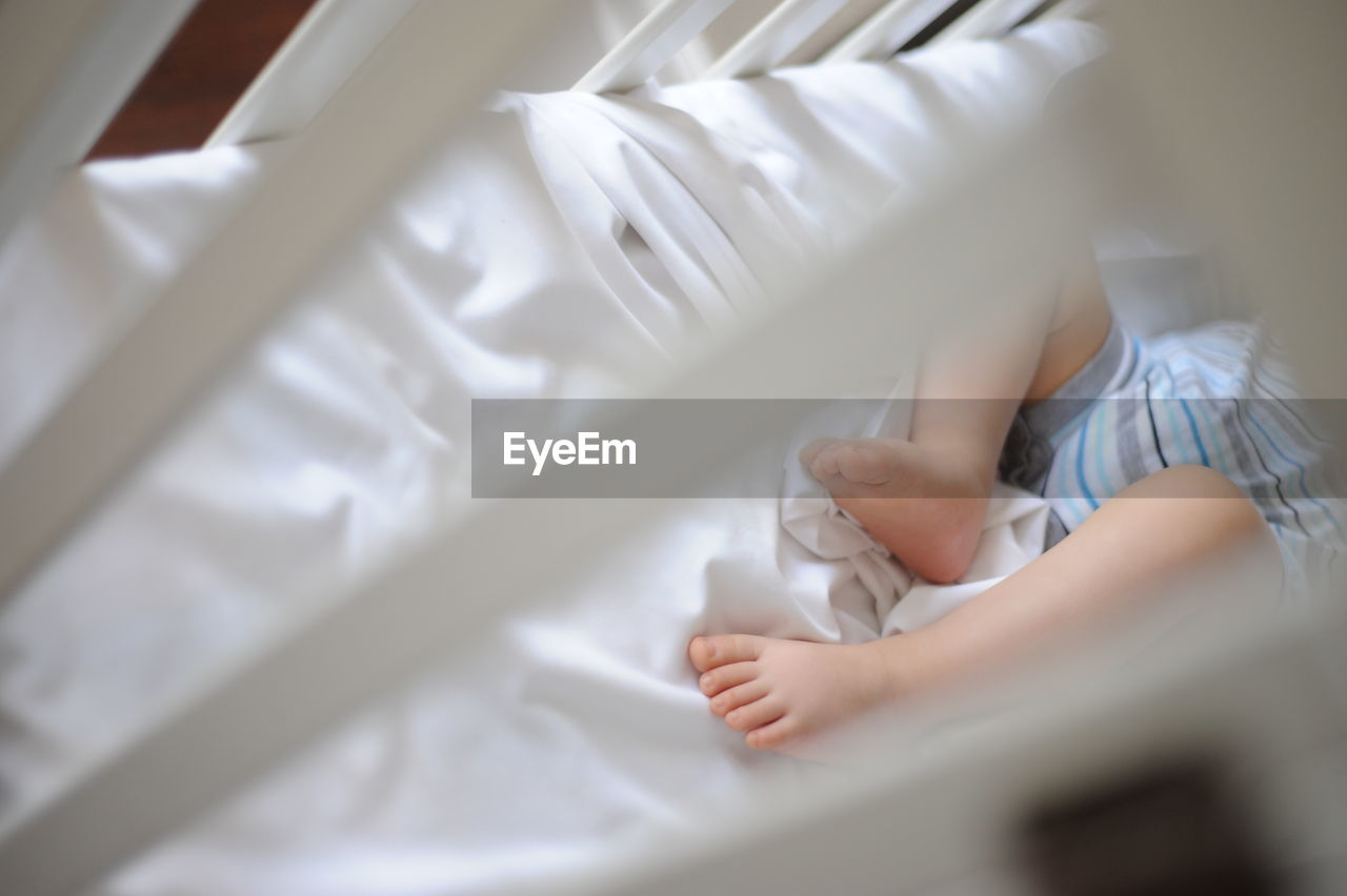 Low section of baby sleeping in crib at home