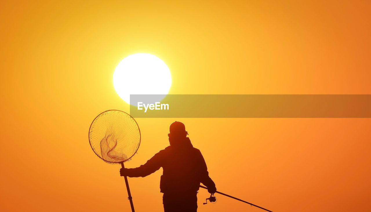Silhouette man holding fishing net and rod against clear orange sky