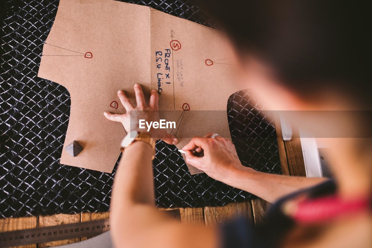 Cropped Image Of Female Fashion Designer Working On Table At Studio
