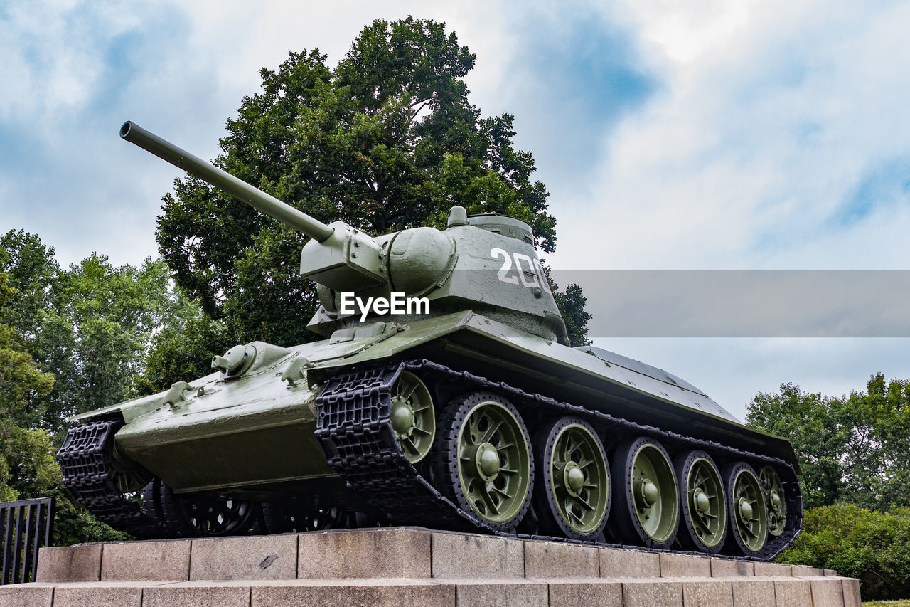 sky, cloud - sky, tree, plant, nature, military, day, armored tank, weapon, no people, transportation, mode of transportation, architecture, history, the past, tank, outdoors, war, armed forces, low angle view, cannon