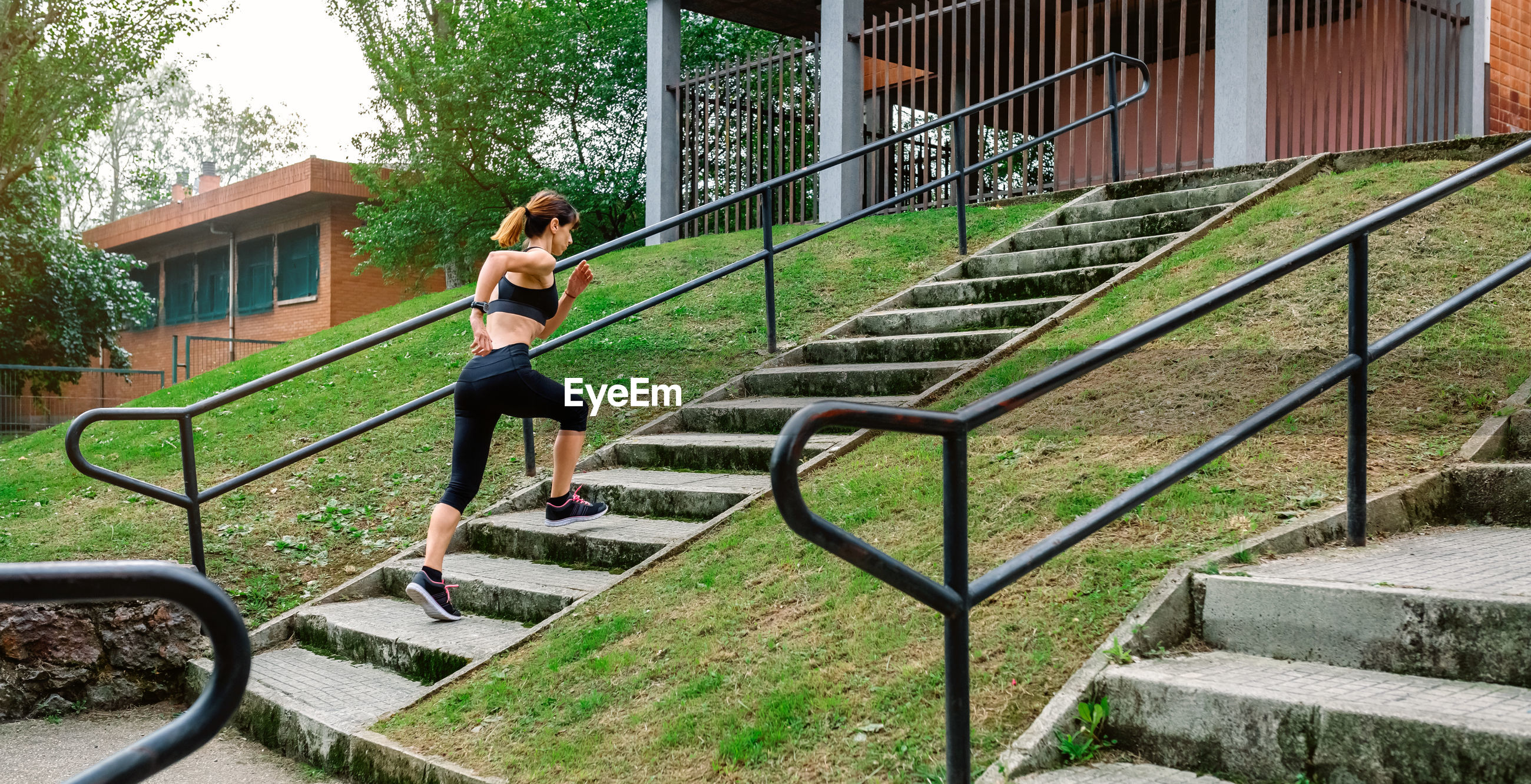 FULL LENGTH OF WOMAN ON STAIRCASE AT PARK