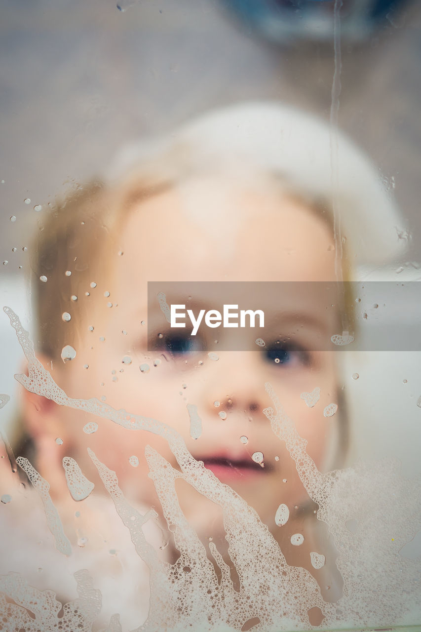 Close-up of toddler covered in soap sud seen through glass