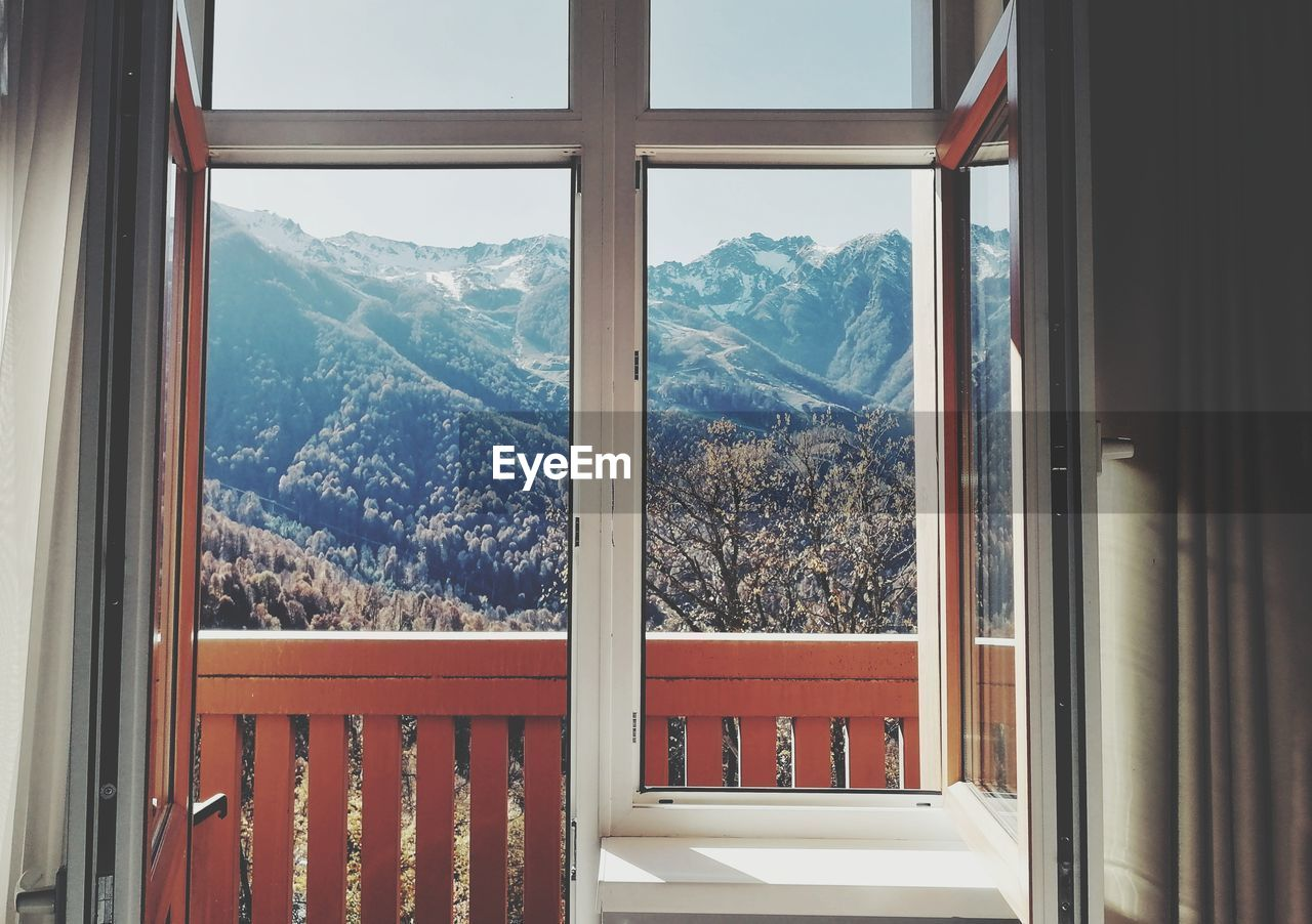 SCENIC VIEW OF MOUNTAINS SEEN THROUGH WINDOW OF BUILDING