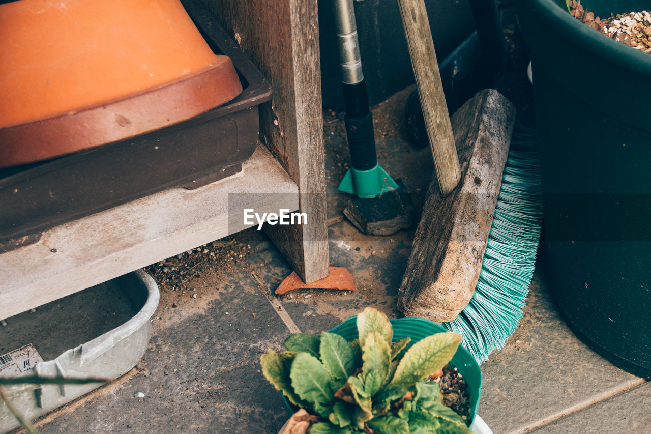 High Angle View Of Broom And Potted Plant By Old Cabinet