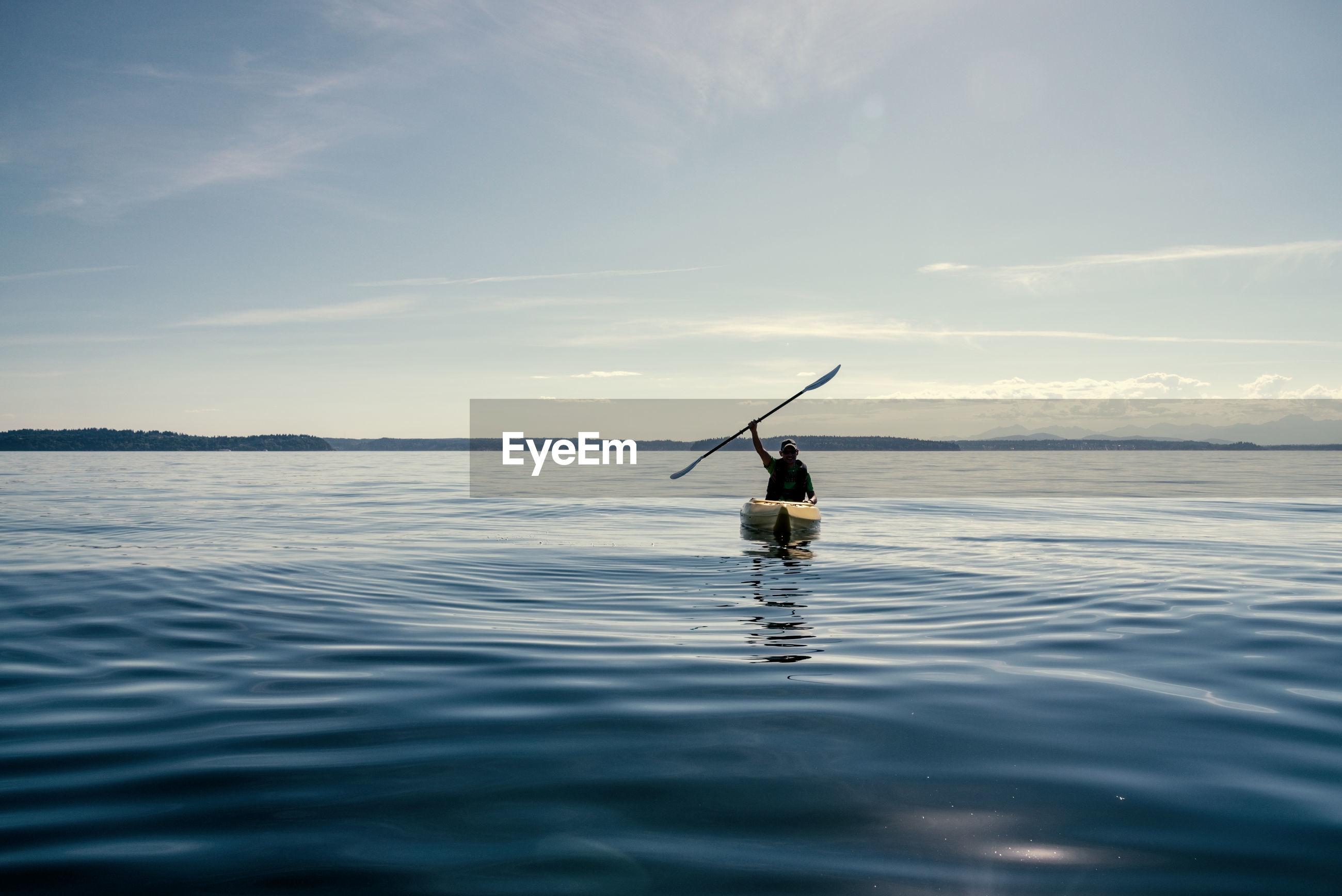 Silhouette man kayaking in sea against sky