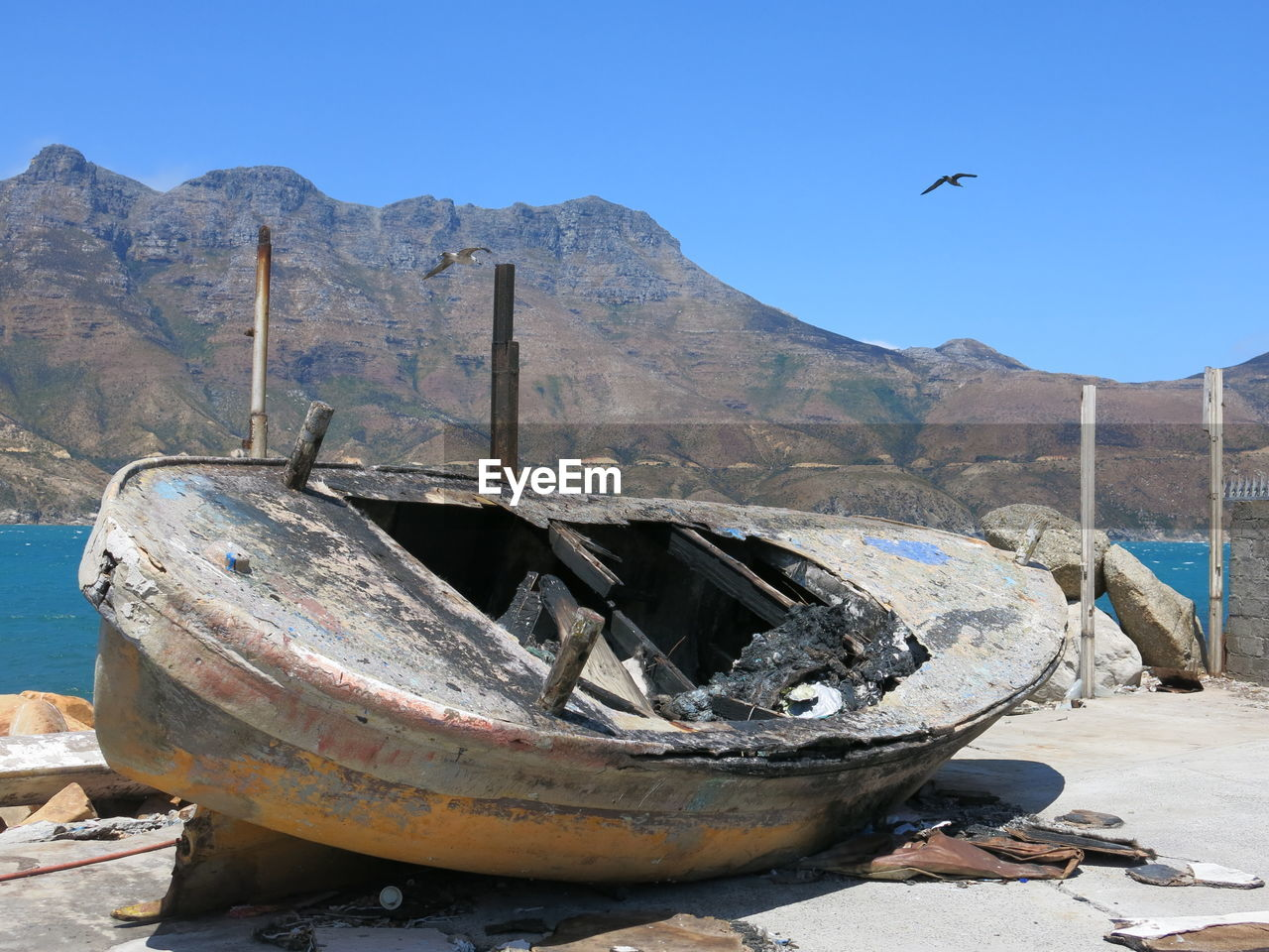 Abandoned Boat By Mountain Against Clear Sky