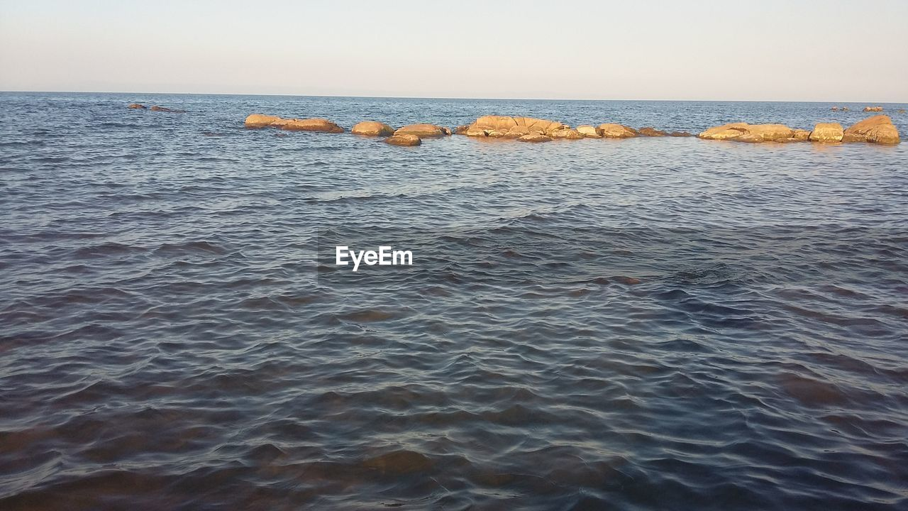 sea, water, horizon over water, sky, horizon, waterfront, beauty in nature, scenics - nature, tranquil scene, tranquility, no people, nature, idyllic, day, rock, rippled, motion, clear sky, non-urban scene, outdoors