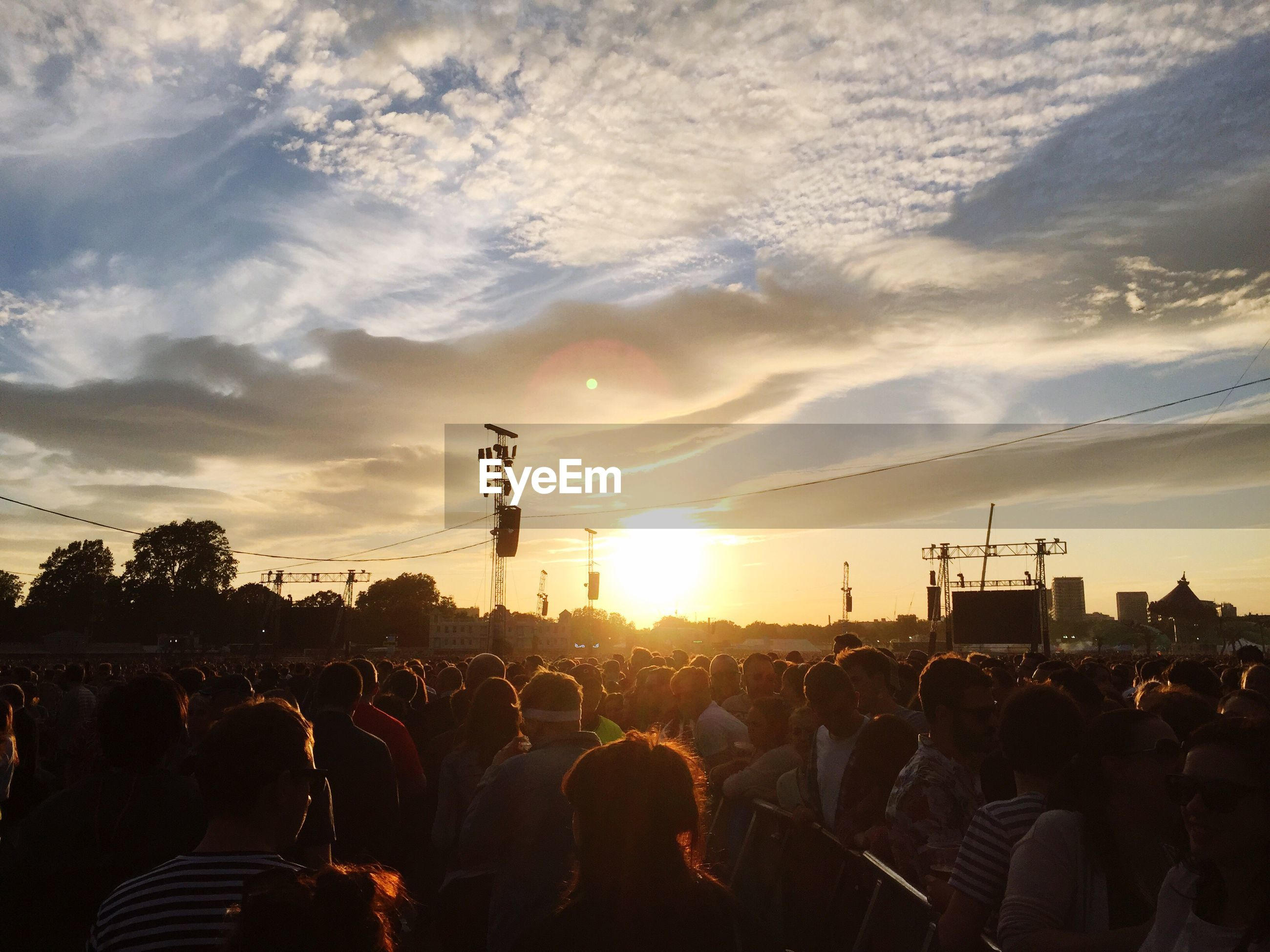 Crowd at music concert against sky during sunset
