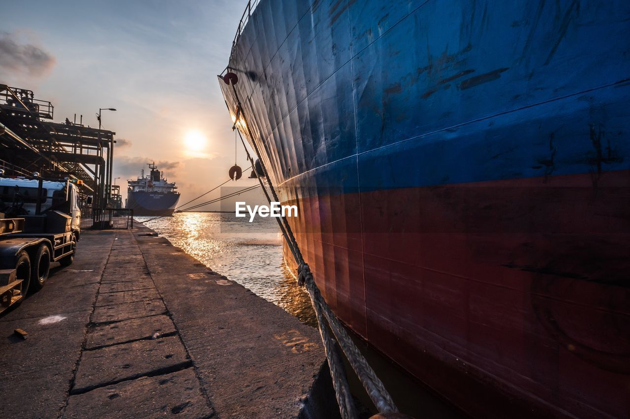 mode of transportation, sky, water, transportation, sunset, architecture, nature, building exterior, nautical vessel, built structure, city, no people, sea, orange color, outdoors, the way forward, sunlight, land vehicle, passenger craft