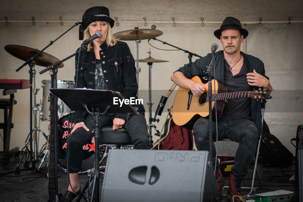 music, musician, real people, hat, playing, musical instrument, performance, singing, singer, drum kit, microphone, performance group, arts culture and entertainment, indoors, guitar, electric guitar, men, drummer, young adult, rock group, day, people