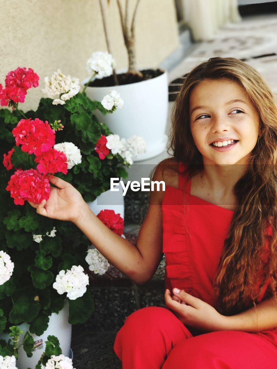 Teenage girl holding flowers while looking away