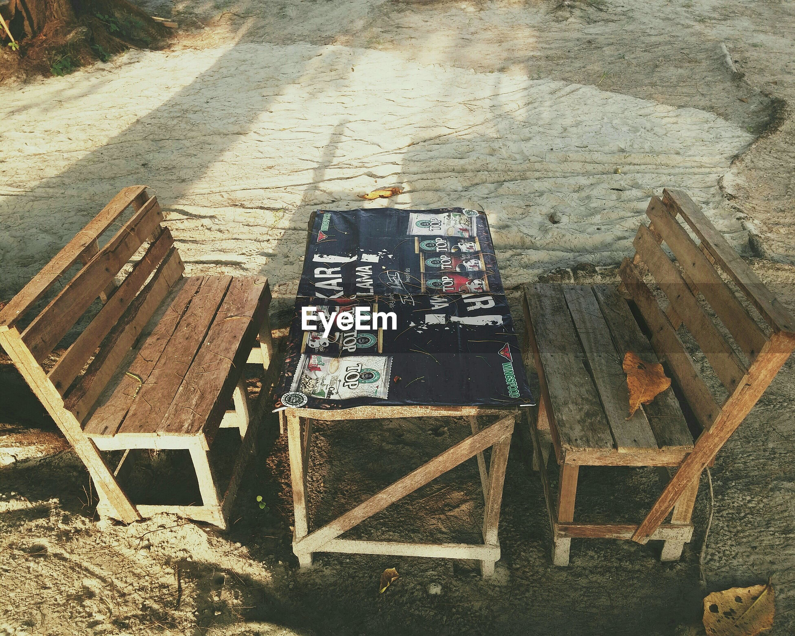 High angle view of wooden chairs and table on field