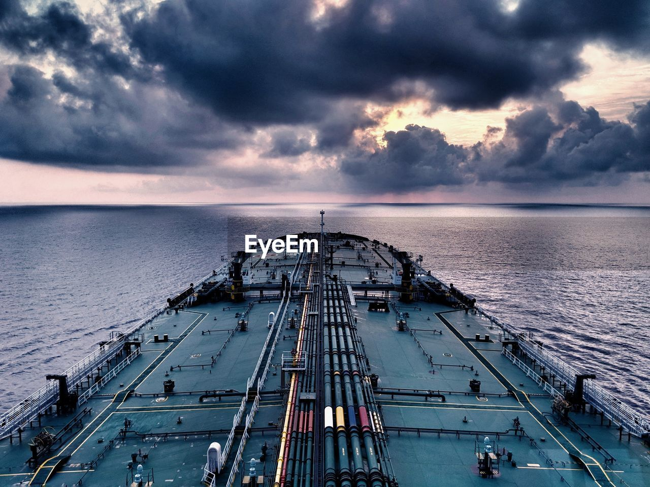 High angle view of container ship sailing on sea against cloudy sky