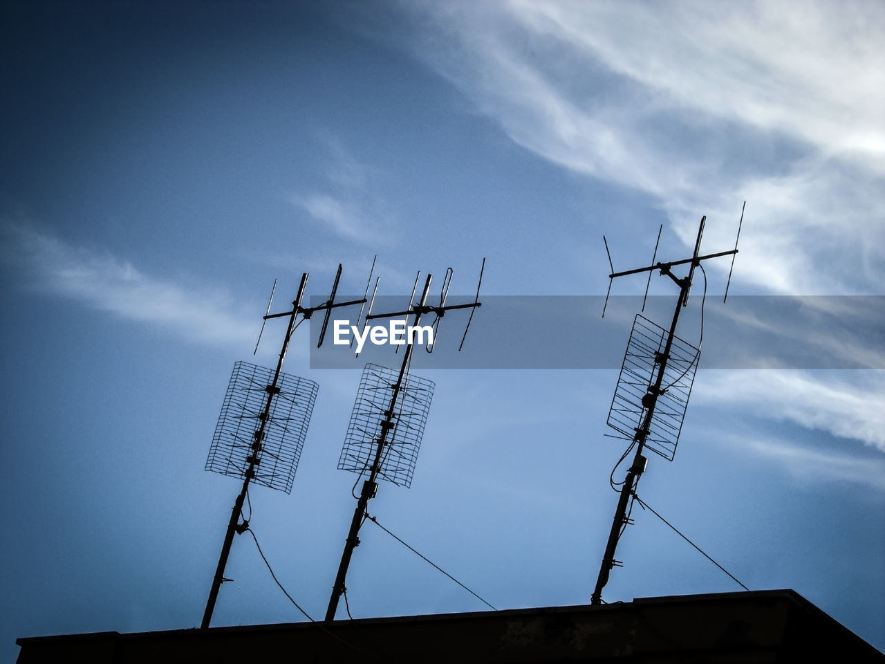 communication, antenna - aerial, connection, low angle view, technology, cloud - sky, television aerial, sky, telecommunications equipment, day, no people, architecture, roof, outdoors, built structure, wireless technology, building exterior