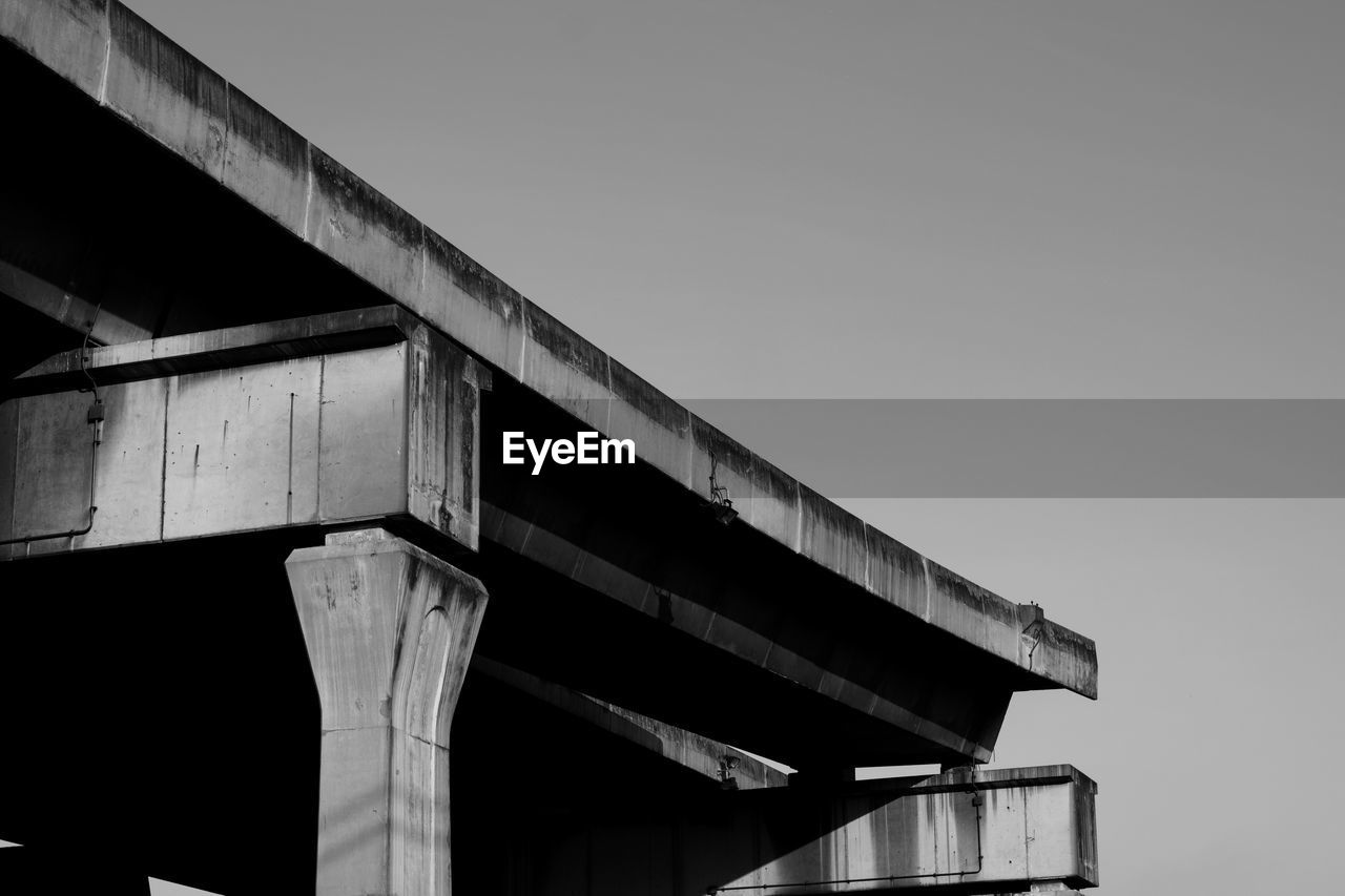 sky, architecture, built structure, low angle view, clear sky, copy space, nature, no people, day, bridge, connection, bridge - man made structure, transportation, building exterior, outdoors, architectural column, sunlight, pattern, elevated road, overpass