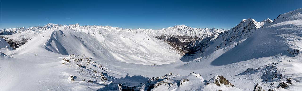 PANORAMIC SHOT OF SNOWCAPPED MOUNTAINS AGAINST CLEAR SKY