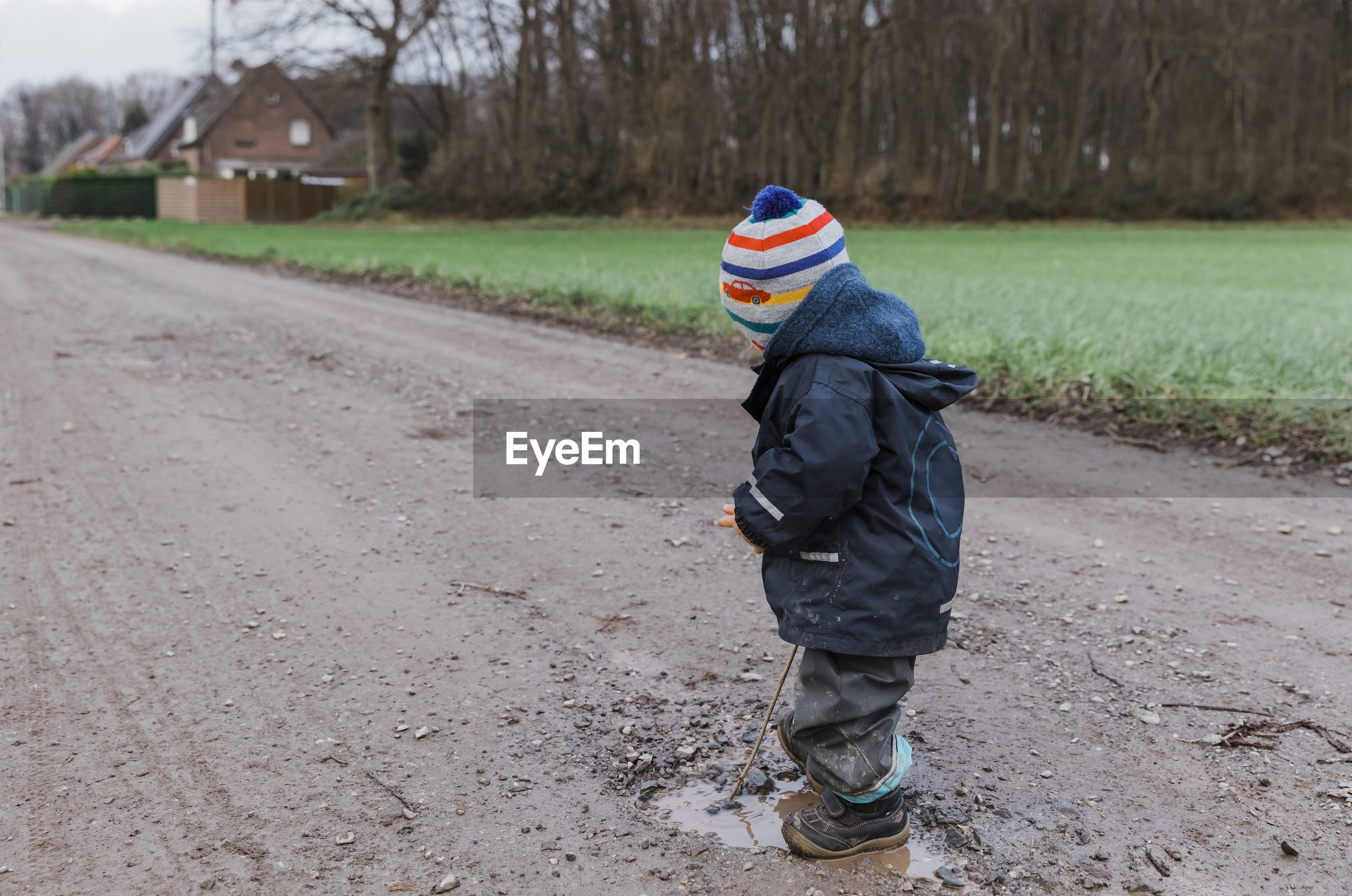 Side view of girl wearing warm clothing standing on dirt road