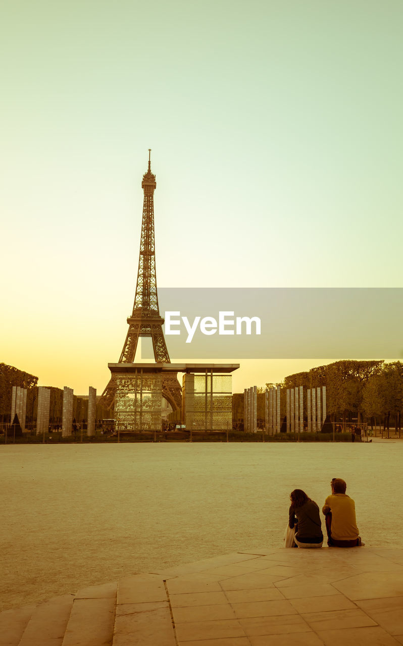 Couple Sitting By River Against Eiffel Tower During Sunset
