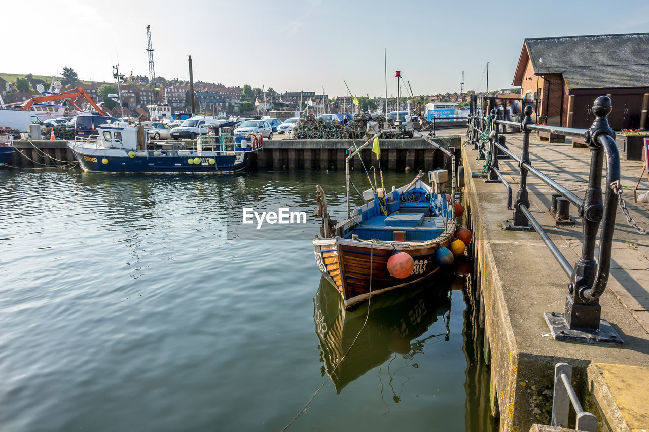 nautical vessel, transportation, mode of transportation, water, moored, waterfront, nature, architecture, reflection, harbor, no people, day, sky, building exterior, built structure, outdoors, sea, clear sky, fishing boat, sailboat, wooden post, fishing industry, port