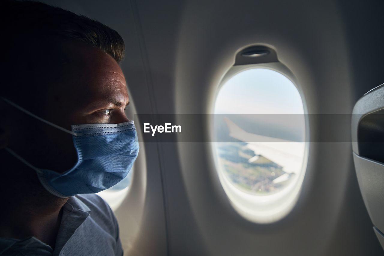 Close-up of man wearing flu mask sitting at airplane
