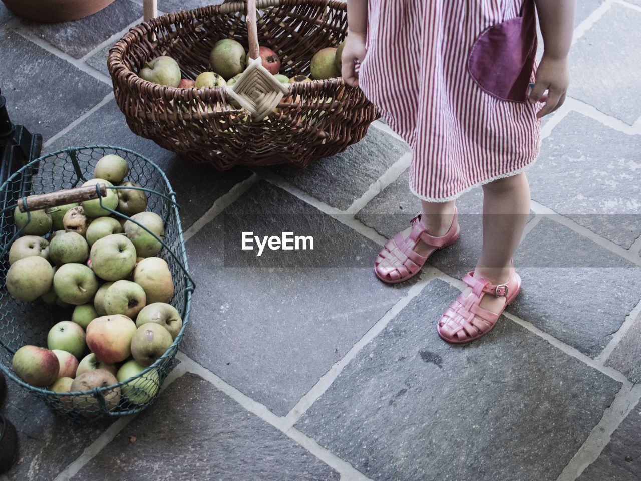 Low Section Of Girl Standing By Apples In Baskets On Footpath