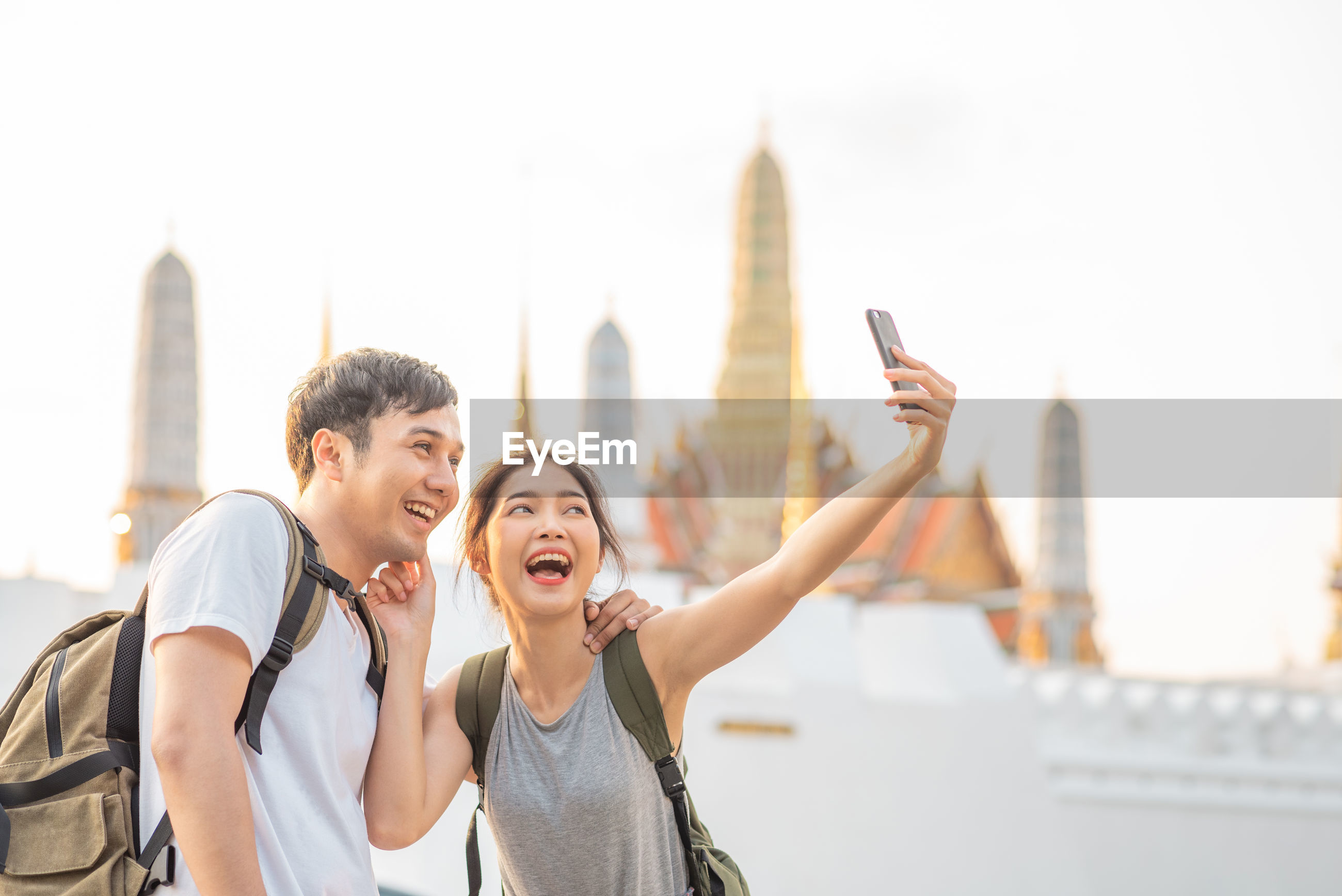 Smiling young couple taking selfie while standing in city