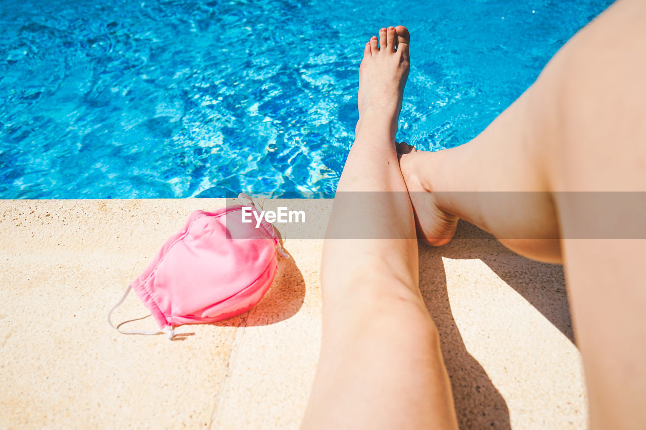 Low section of woman with mask sitting at poolside