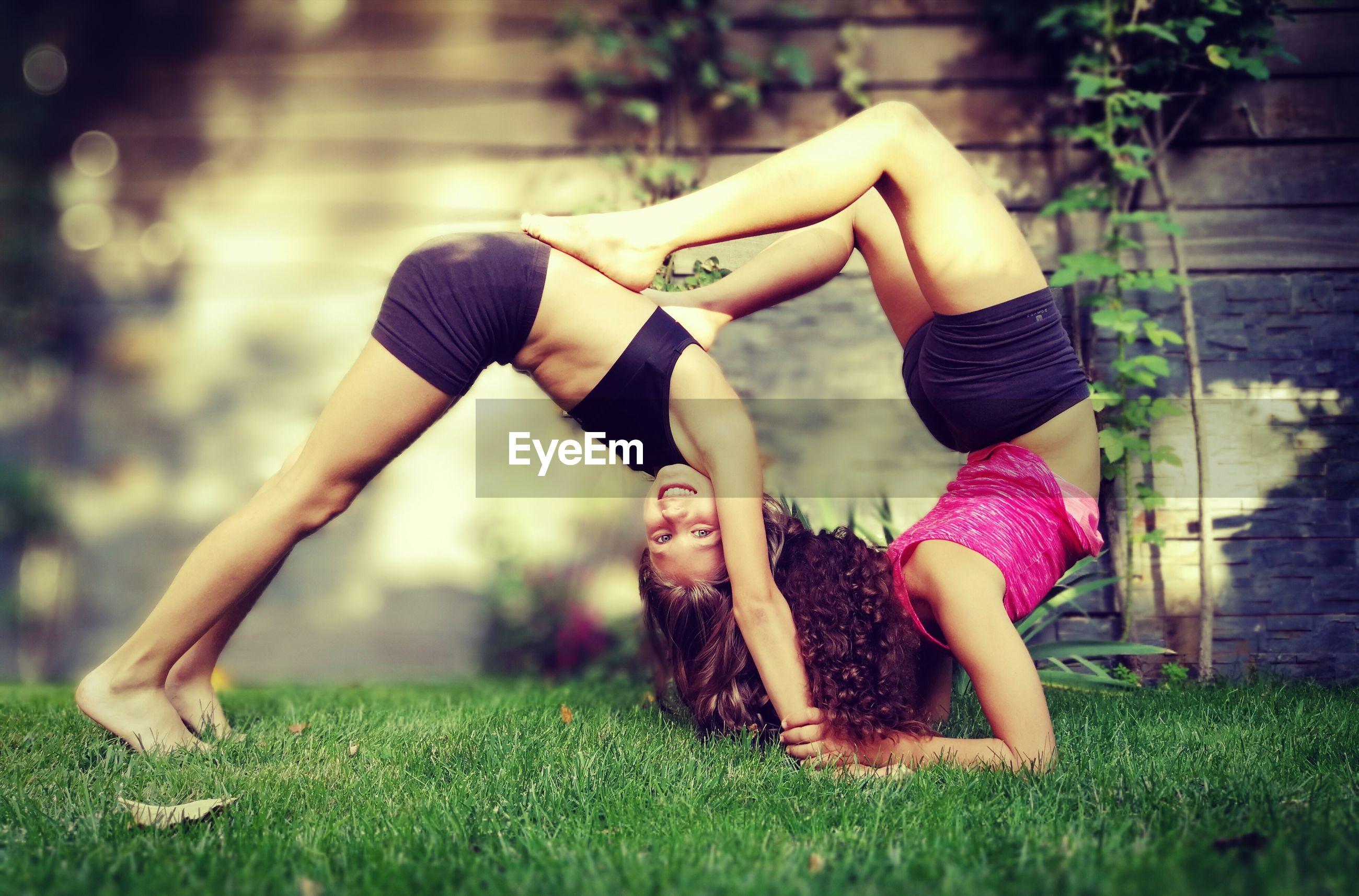 Full length of flexible friends exercising on grassy field