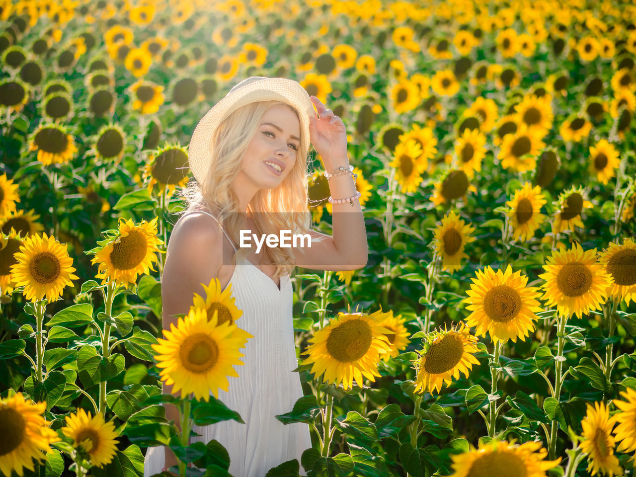 Young Woman Standing At Sunflower Field