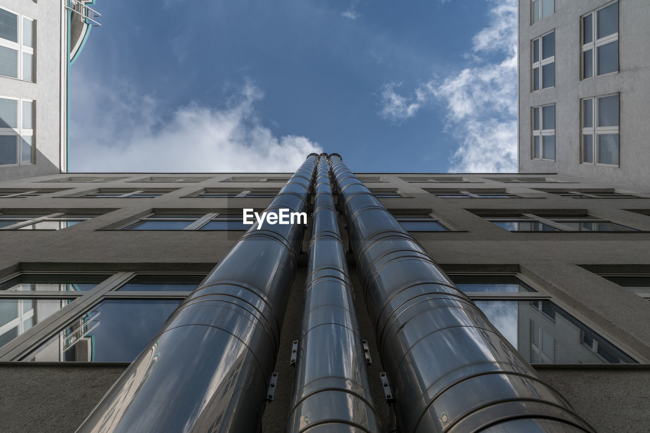 Directly Below Shot Of Metal Pipes On Buildings Against Sky