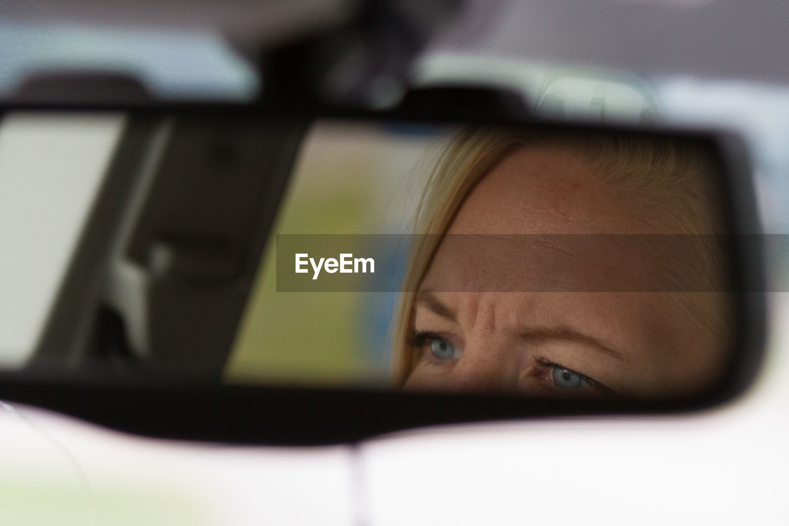 Woman reflecting on rear-view mirror of car