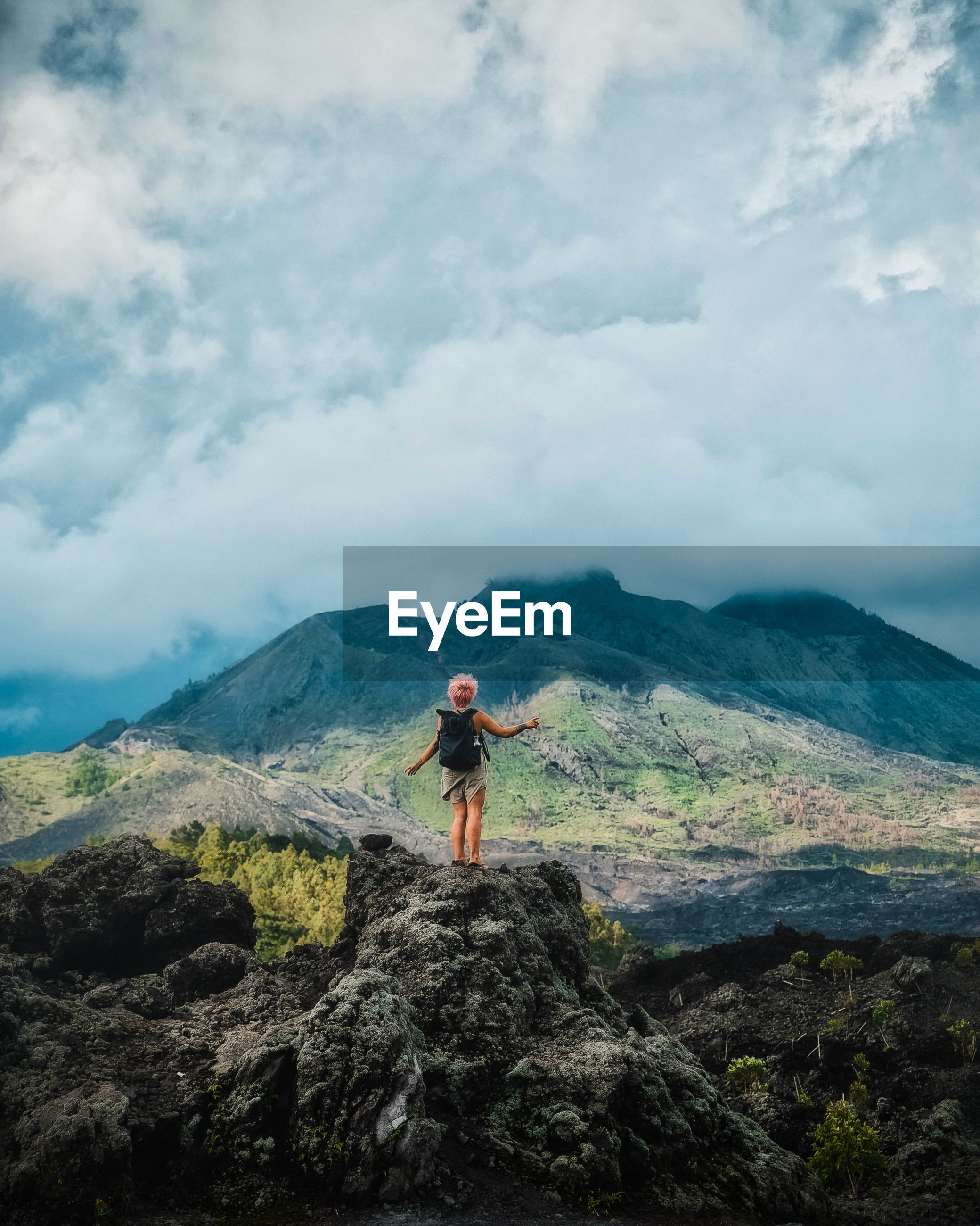Hiker standing on rock looking at mountain against sky