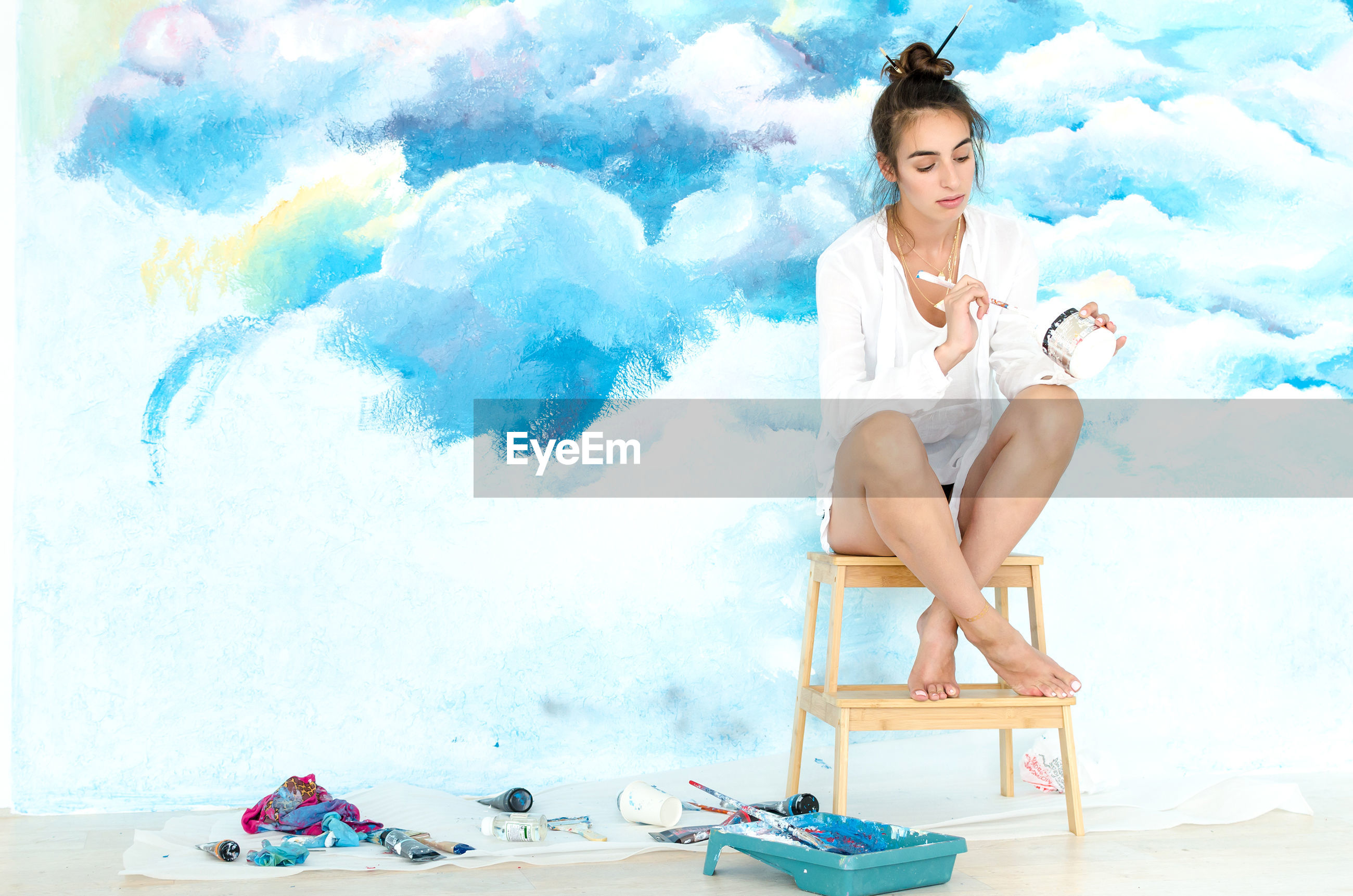 DIGITAL COMPOSITE IMAGE OF WOMAN SITTING ON TABLE AGAINST WALL