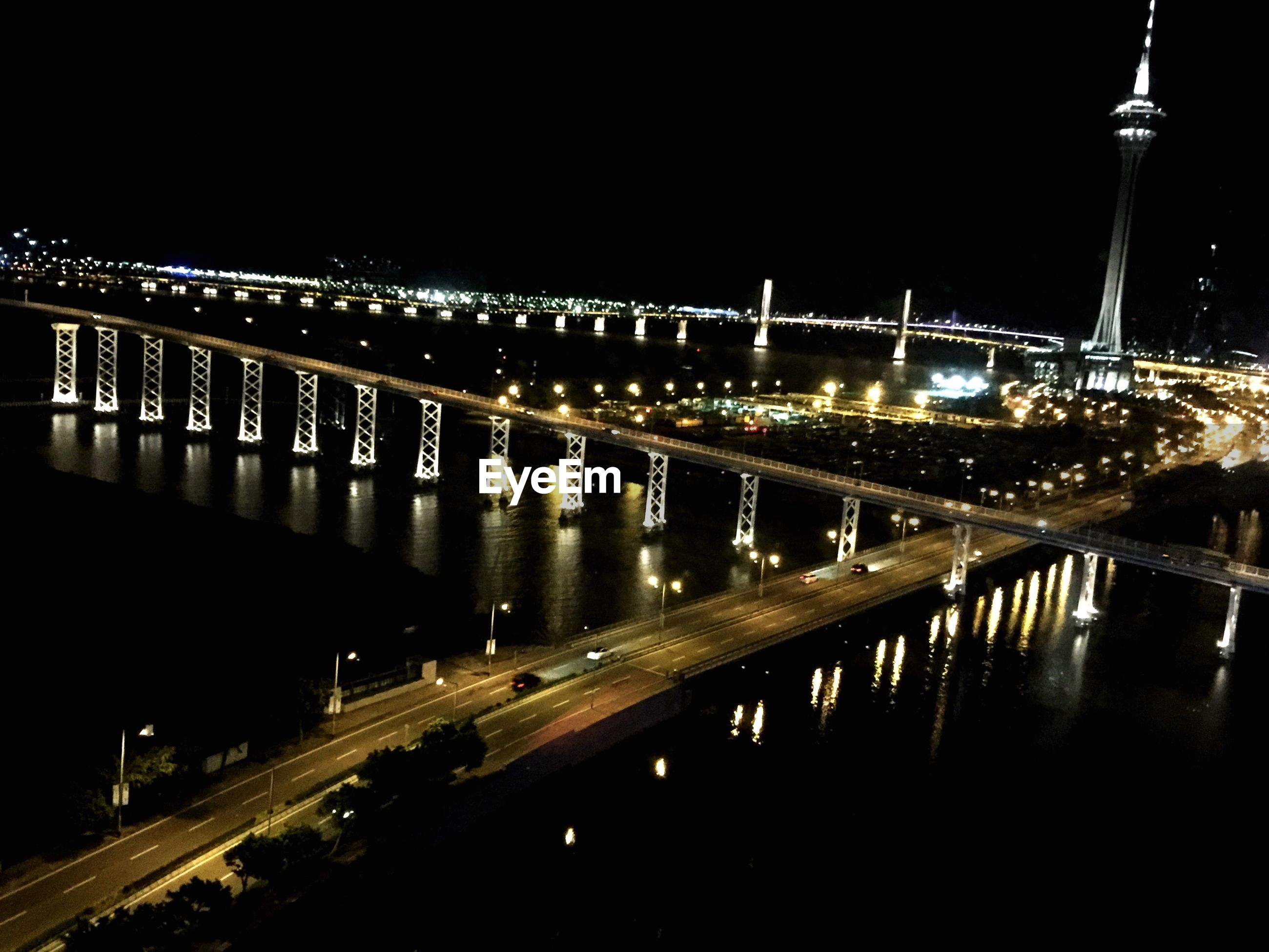 Illuminated macau tower against sky in city at night