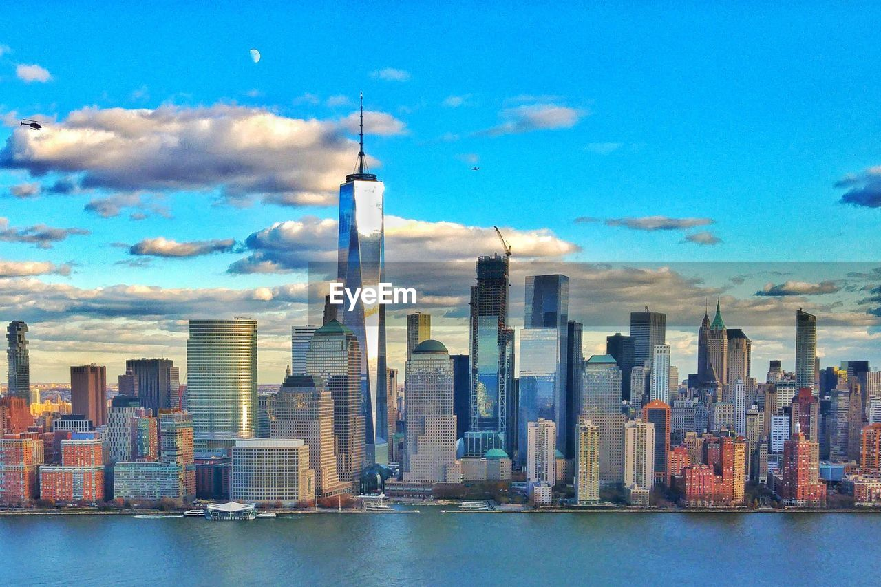 skyscraper, architecture, city, building exterior, built structure, tower, travel destinations, sky, skyline, cityscape, outdoors, water, no people, development, tall, urban skyline, downtown district, modern, financial district, day, sea, cloud - sky