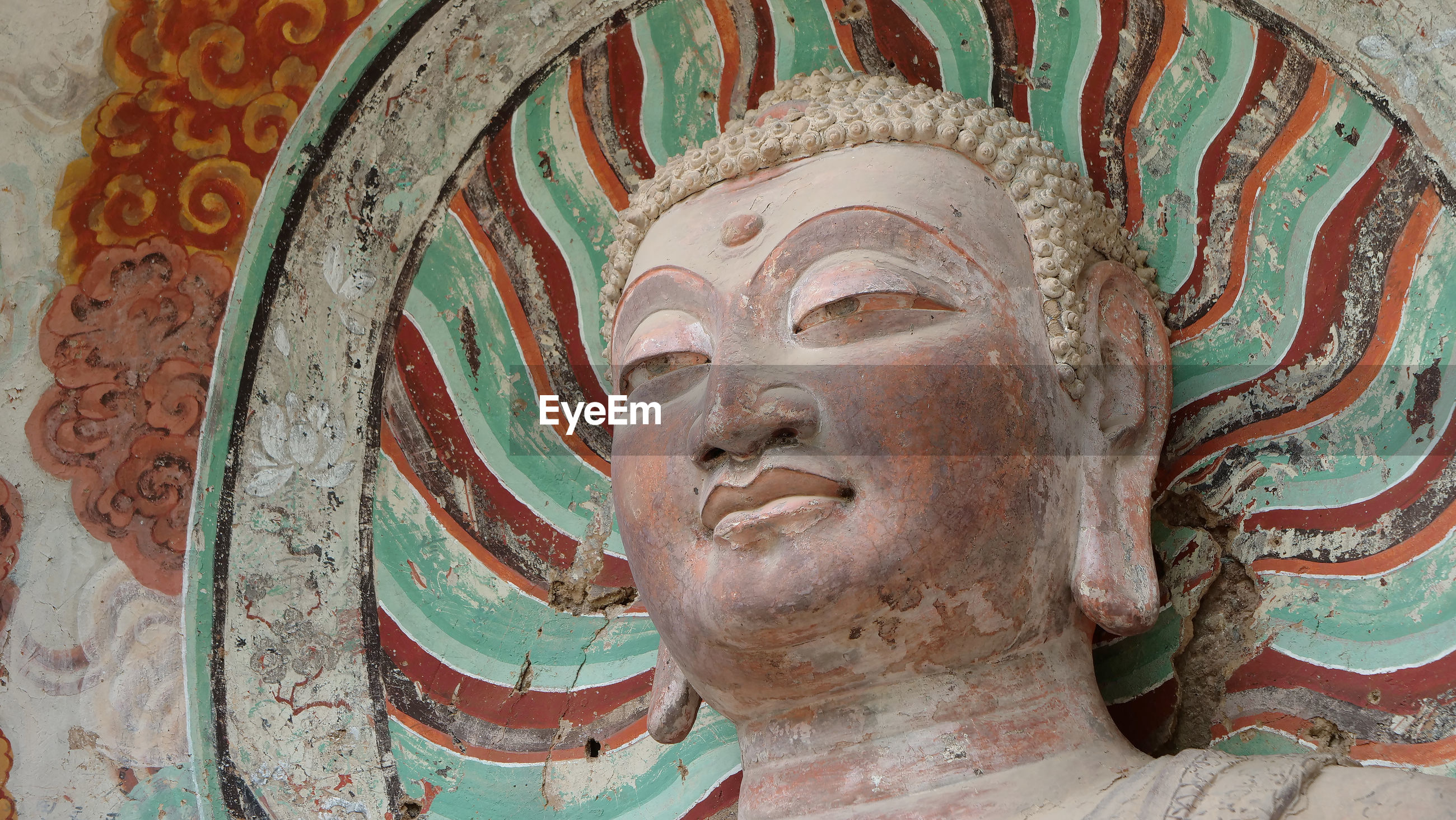 CLOSE-UP OF BUDDHA STATUE AGAINST TEMPLE BUILDING