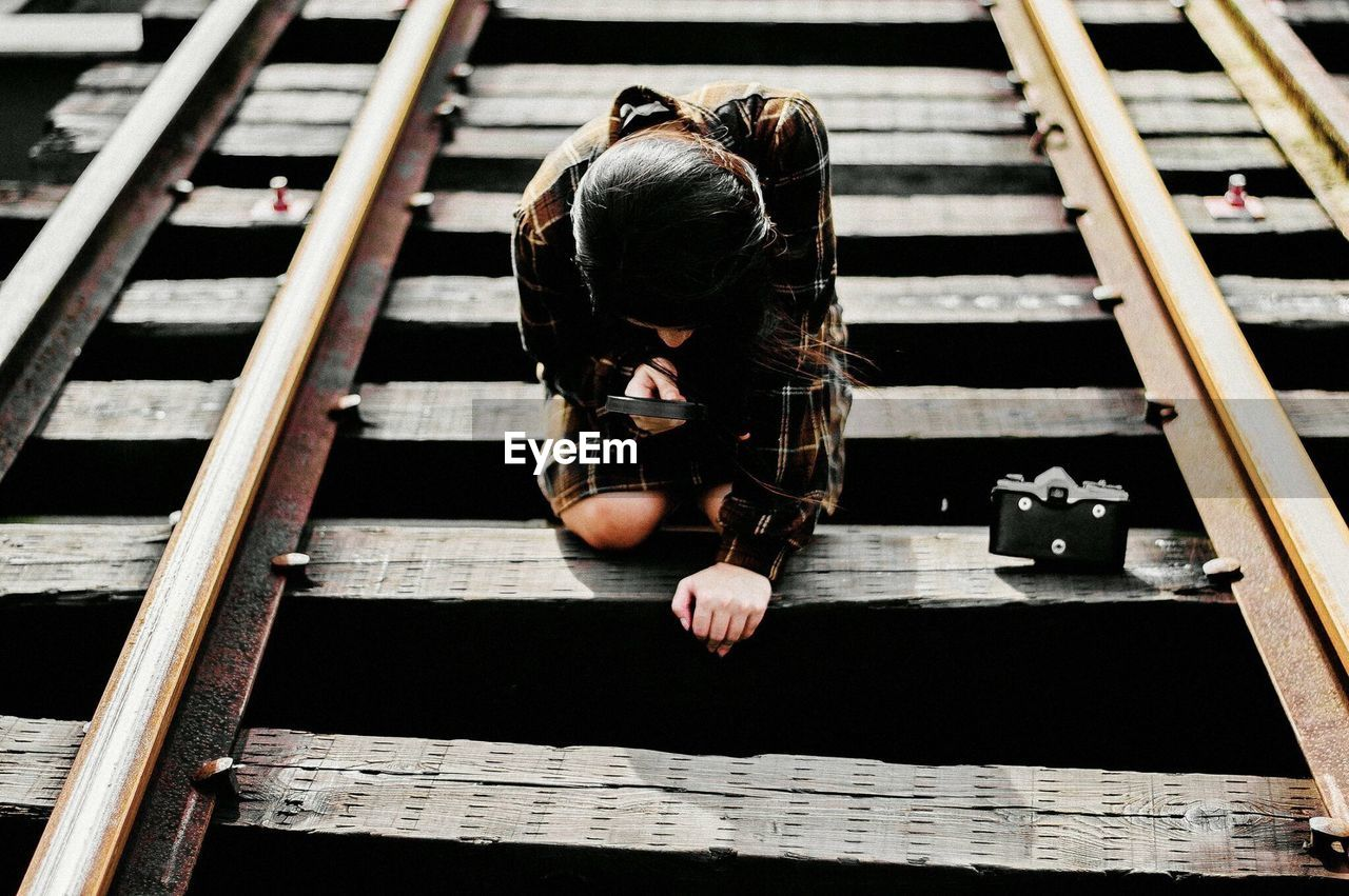 real people, railroad track, wood - material, sitting, transportation, men, one person, full length, day, outdoors, working, adult, people