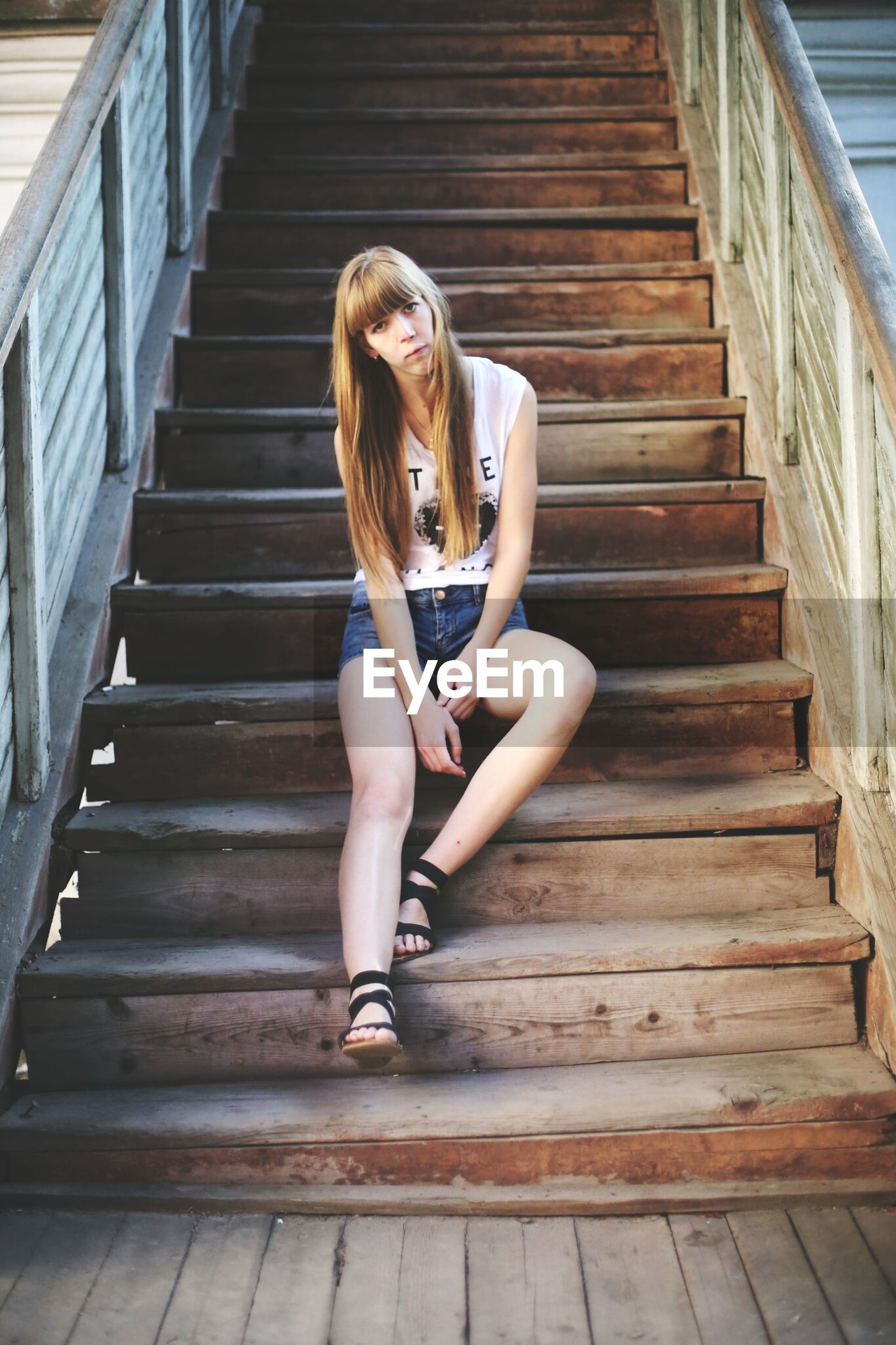 full length, lifestyles, leisure activity, young adult, person, casual clothing, young women, wood - material, standing, childhood, front view, girls, steps, side view, elementary age, wooden, holding, built structure