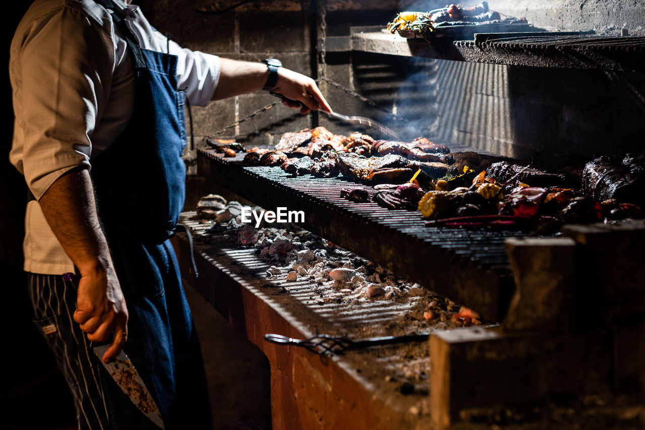 Midsection of chef preparing food on barbecue grill