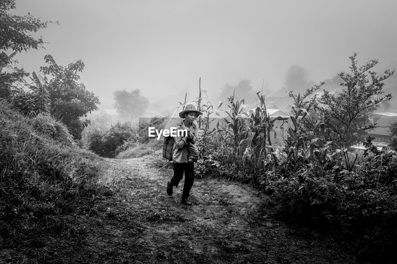 plant, tree, one person, full length, real people, walking, land, lifestyles, nature, sky, rear view, day, leisure activity, men, casual clothing, growth, field, outdoors, standing
