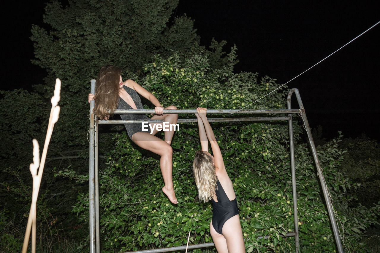 Young woman on tree against sky at night