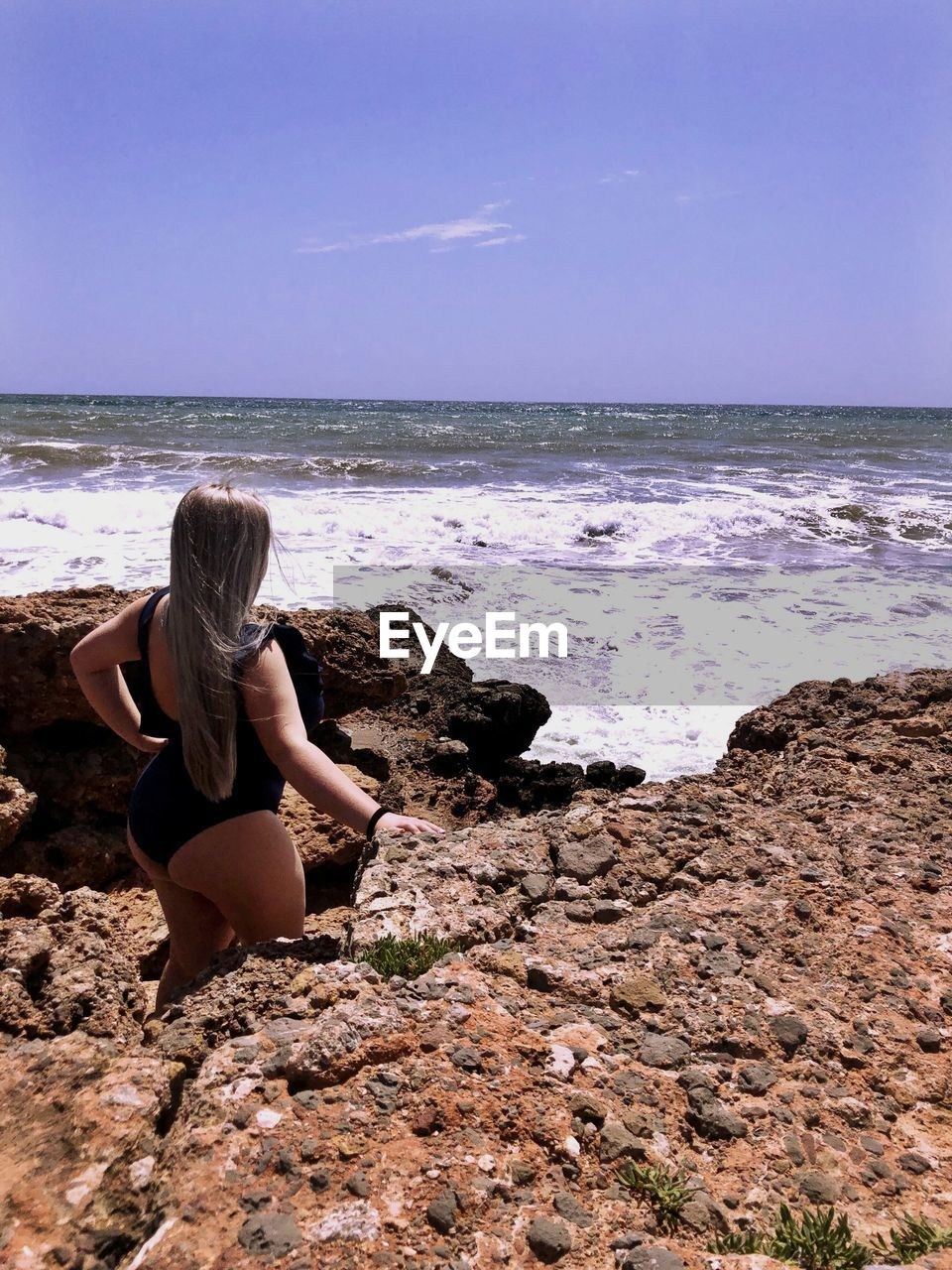 Woman standing amidst rocks at beach against sky