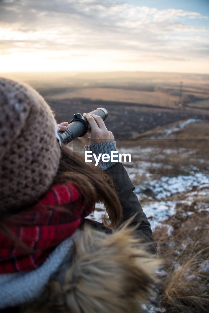 Rear View Of Woman Looking Through Binoculars Against Sky