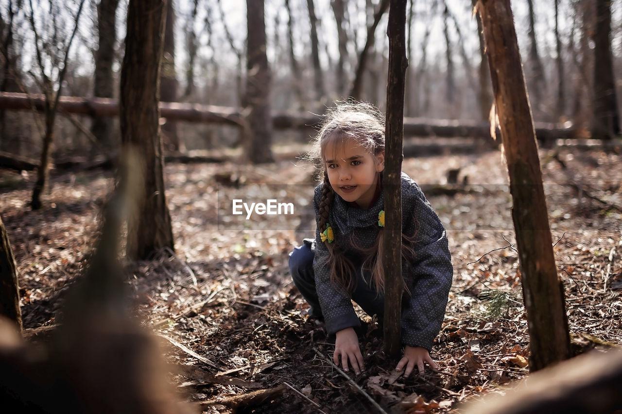 FULL LENGTH OF GIRL IN FOREST AGAINST TREES