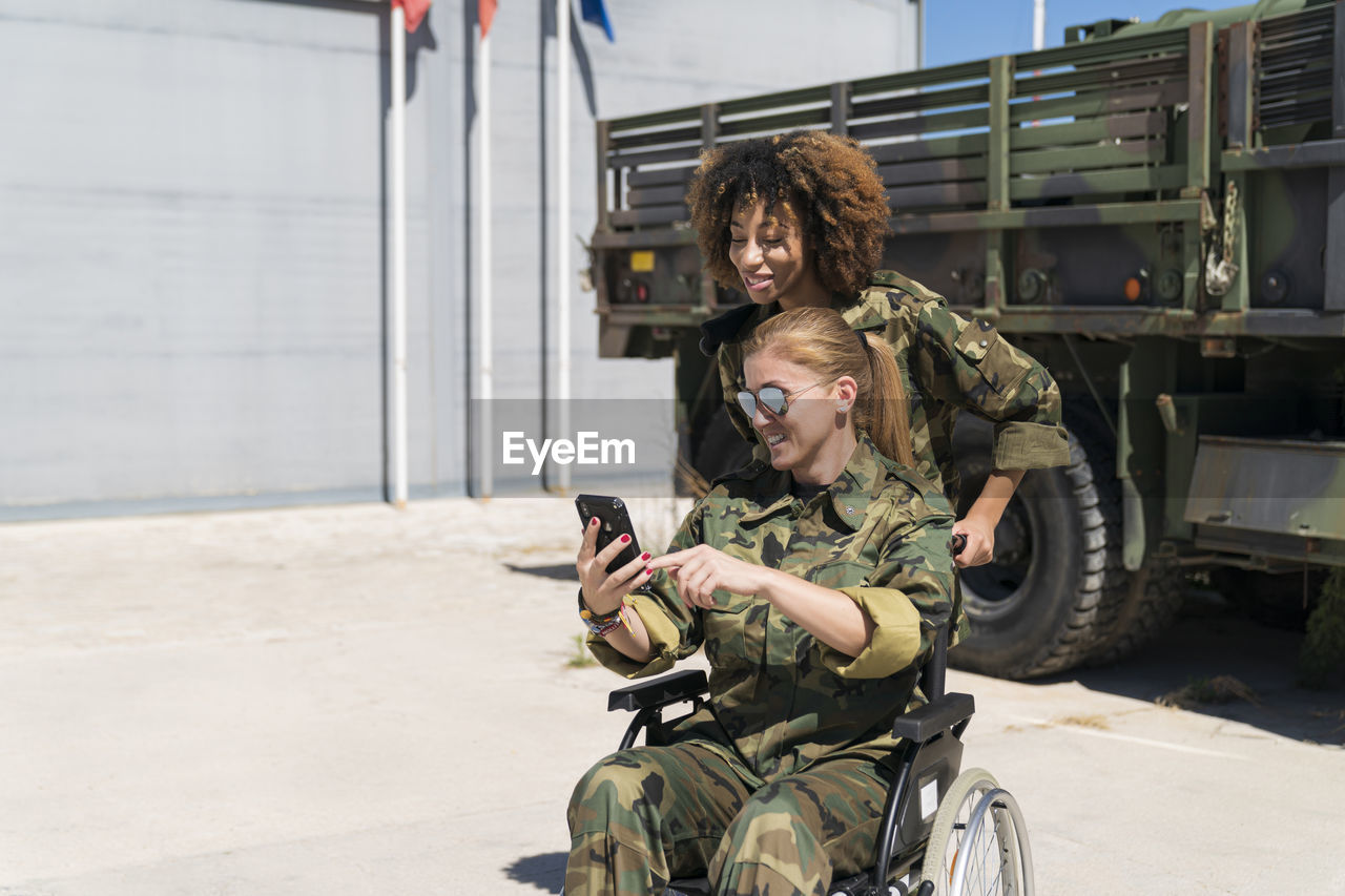YOUNG WOMAN USING MOBILE PHONE WHILE SITTING ON MOTORCYCLE