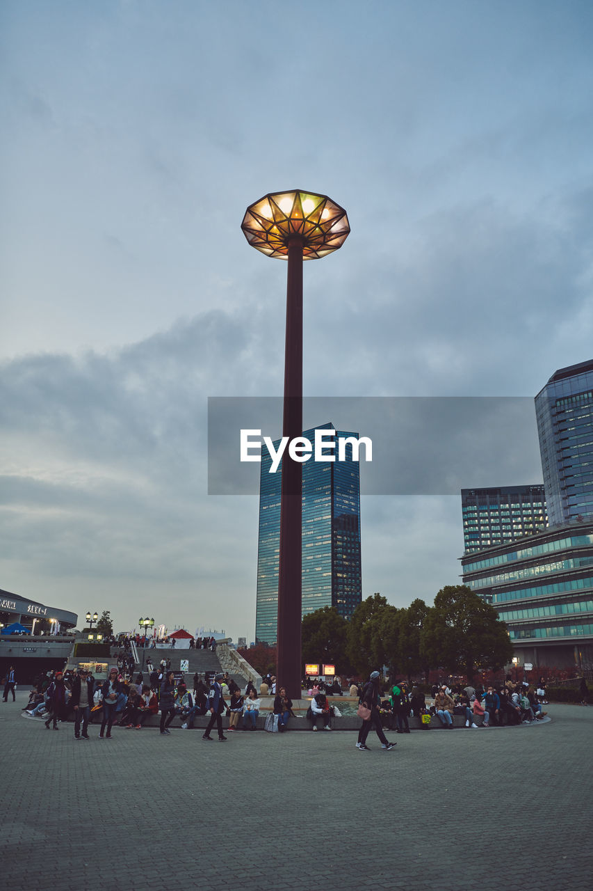 building exterior, architecture, built structure, city, group of people, crowd, real people, street, sky, tall - high, large group of people, cloud - sky, lighting equipment, office building exterior, women, street light, adult, nature, lifestyles, skyscraper, light