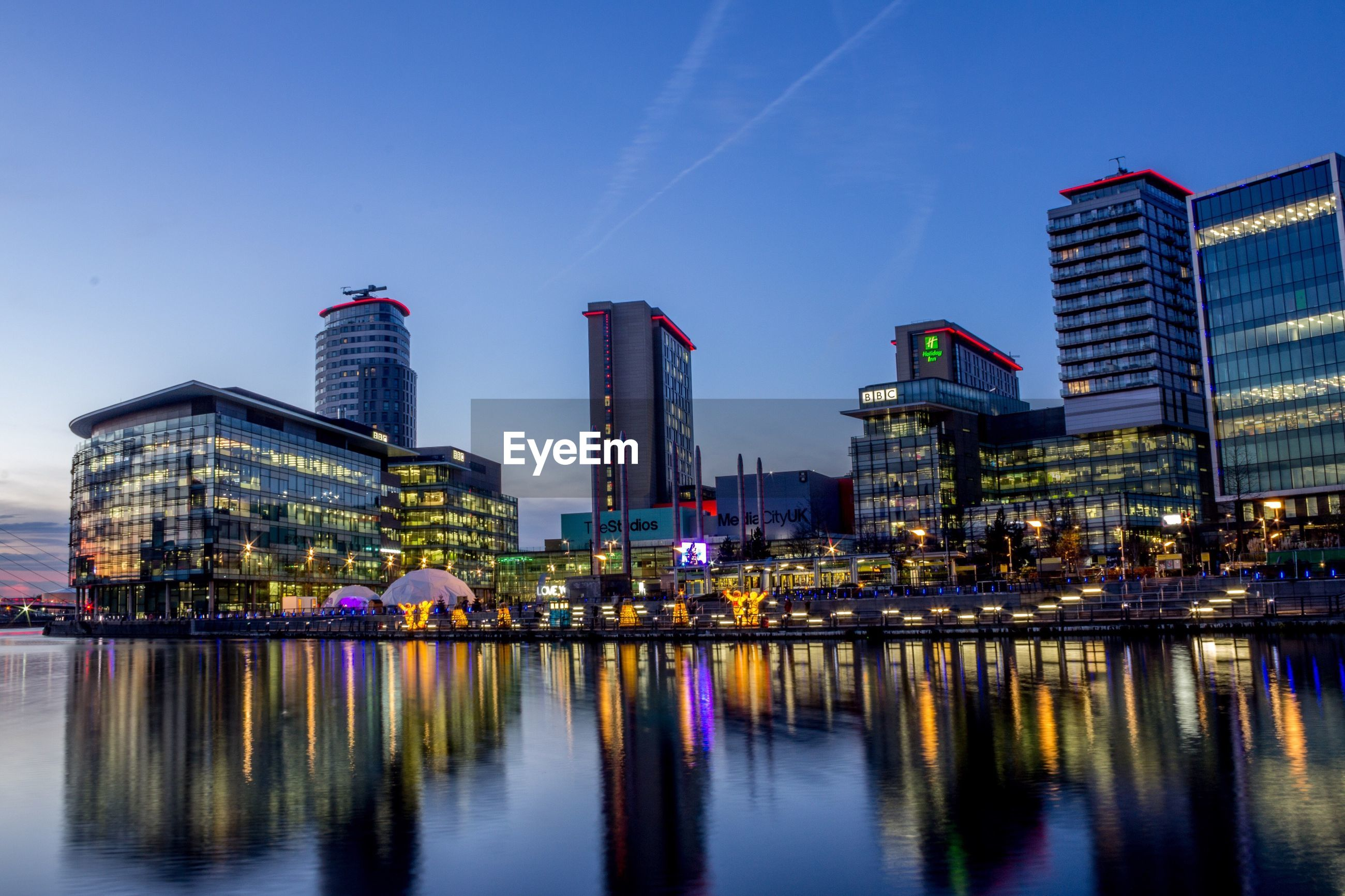 reflection, illuminated, city, building exterior, architecture, night, waterfront, skyscraper, urban skyline, built structure, modern, water, outdoors, travel destinations, bridge - man made structure, river, cityscape, sky, no people, nautical vessel