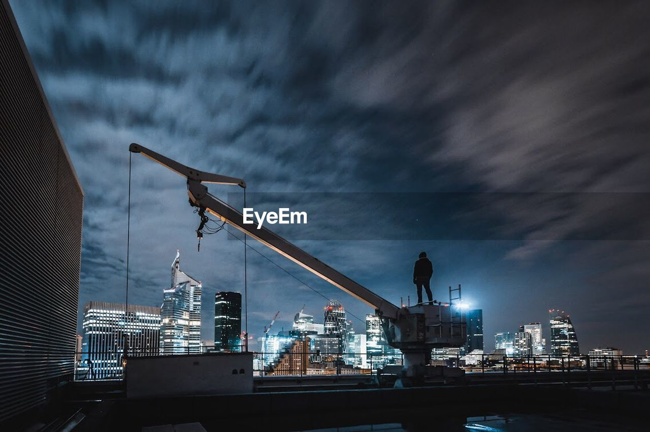 architecture, cloud - sky, sky, building exterior, built structure, nature, industry, machinery, crane - construction machinery, dusk, illuminated, construction industry, pier, water, outdoors, commercial dock, harbor, city, no people, development, cityscape, skyscraper, construction equipment